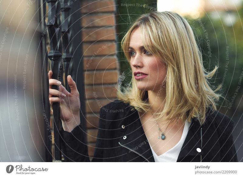 Blondine, die im städtischen Hintergrund mit verlorenem Blick stehen schön Haare & Frisuren Gesicht Mensch Frau Erwachsene Straße Mode Jeanshose Jacke blond