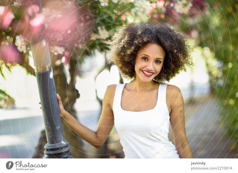 Gemischte Frau mit Afro-Frisur, die im Stadtpark lächelt. Lifestyle Stil Glück schön Haare & Frisuren Gesicht Sommer Mensch feminin Junge Frau Jugendliche