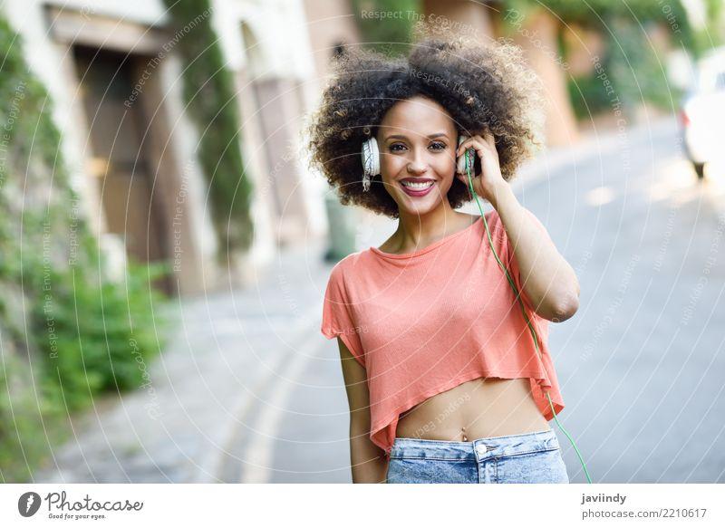 Porträt eines jungen, attraktiven schwarzen Mädchens im städtischen Hintergrund, das der Musik mit Kopfhörern lauscht. Lifestyle Freude Glück schön