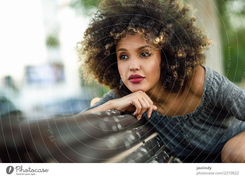 Schwarze Frau mit Afro-Frisur, die auf einer Bank sitzt. Lifestyle Stil Glück schön Haare & Frisuren Gesicht Mensch Erwachsene Straße Mode Kleid Afro-Look