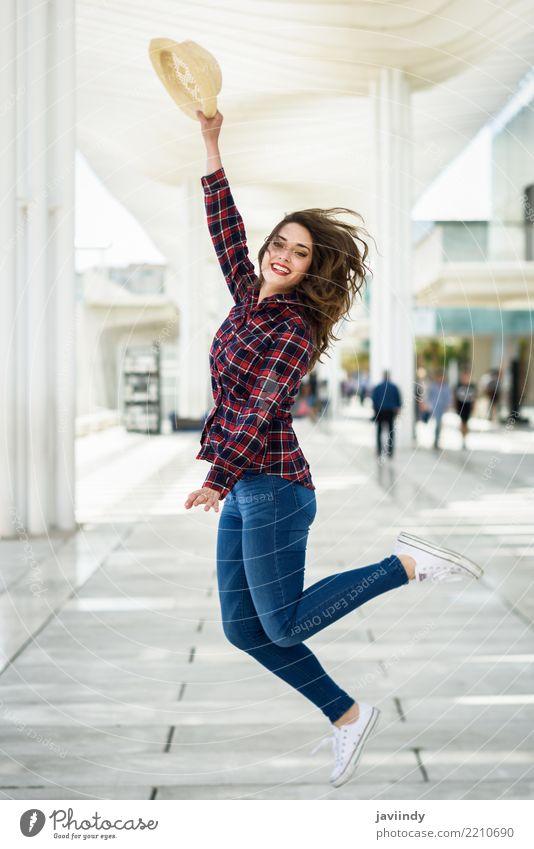 Das Mädchen springend in städtischen Hintergrund. Frau Mensch Sommer schön weiß Erwachsene Stil Glück Mode Lächeln Fröhlichkeit Beautyfotografie Model Hut Hemd