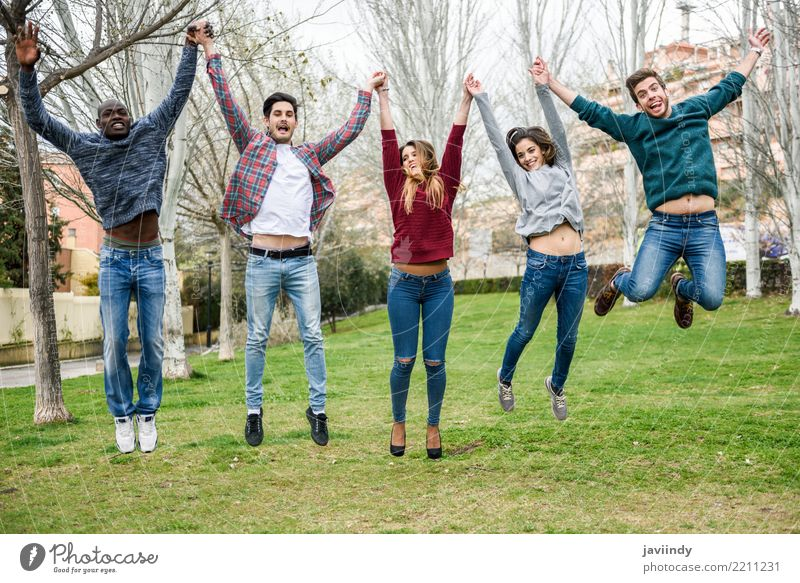 Mehrrassige junge Menschen, die gemeinsam im Freien springen. Lifestyle Freude Frau Erwachsene Mann Freundschaft 5 Menschengruppe 18-30 Jahre Jugendliche Park