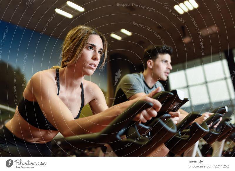 Paare in einer spinnenden klasse tragenden Sportkleidung. Cyclo Innen. Frau Mensch Jugendliche Mann 18-30 Jahre Erwachsene Lifestyle feminin Menschengruppe