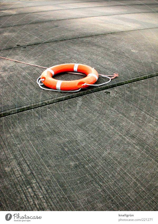 Lebensretter grau orange Seil Hoffnung Sicherheit rund liegen außergewöhnlich Rettung Überleben Rettungsring Notruf SOS Sanitäter Betonboden