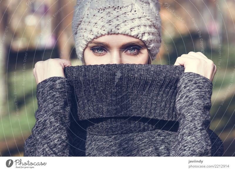 Frau, die in einem Park mit Winterwollkappe steht Mensch blau schön weiß Erwachsene Straße Lifestyle Herbst feminin Stil Haare & Frisuren Mode modern