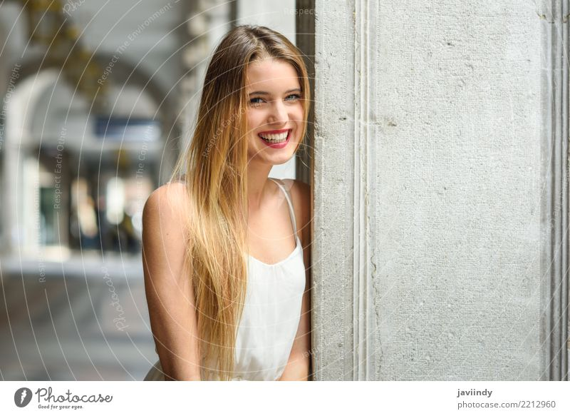 Lächelndes blondes Mädchen, das zufällige Kleidung im städtischen Hintergrund trägt Frau Mensch Jugendliche Sommer schön weiß Erotik Freude 18-30 Jahre Gesicht