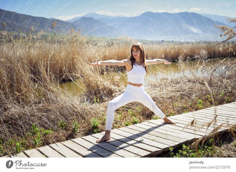 Junge Frau, die Yoga in der Natur tut. Lifestyle schön Wellness Erholung Meditation Sommer Sport Mensch Erwachsene Fitness dünn weiß Krieger Pose 2 Hintergrund