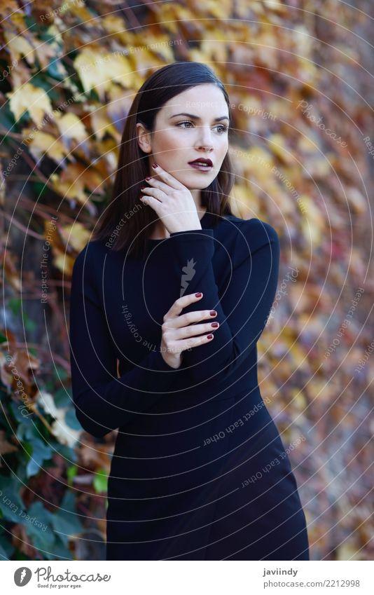 Frau, die schwarzes Kleid mit Herbstfarben am Hintergrund trägt Lifestyle Stil Glück schön Haare & Frisuren Mensch Erwachsene Straße Mode trendy modern weiß