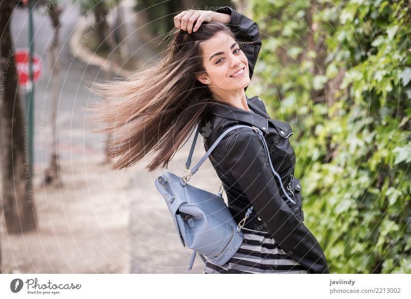 Junge Frau, die ihr Haar im städtischen Hintergrund bewegt Lifestyle Stil Glück schön Haare & Frisuren Mensch Erwachsene Wind Straße Mode Rock Jacke Leder