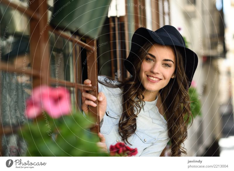 Junge Frau, die mit Hut nahe einem Fenster lächelt Lifestyle elegant Stil Glück schön Haare & Frisuren Gesicht Mensch Erwachsene Straße Mode Hemd brünett