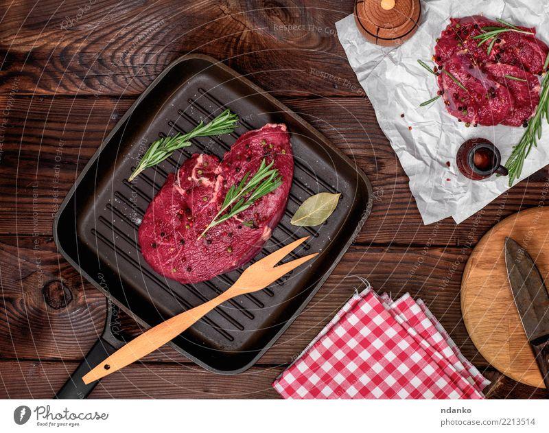 frisches Rindersteak mit Rosmarin Fleisch Kräuter & Gewürze Abendessen Gabel Tisch Papier Holz grün rot Rindfleisch Blut hacken geschnitten Feinschmecker