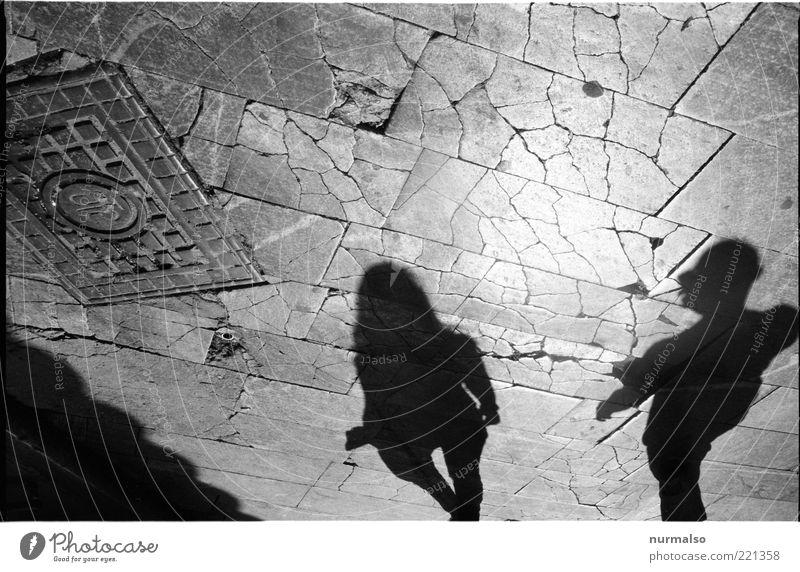 Geschichte begehen Mensch Jugendliche alt Erwachsene Junge Frau Paar Junger Mann Platz Boden Bodenbelag gebrochen Partner Pflastersteine Fußgänger Gully Schattenspiel