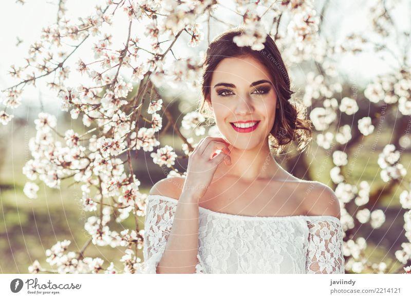 Frau, die im Frühjahr in der geblühten Zeit des Gartens lächelt Mensch Natur schön weiß Baum Blume Gesicht Erwachsene Blüte Stil Glück Haare & Frisuren Mode