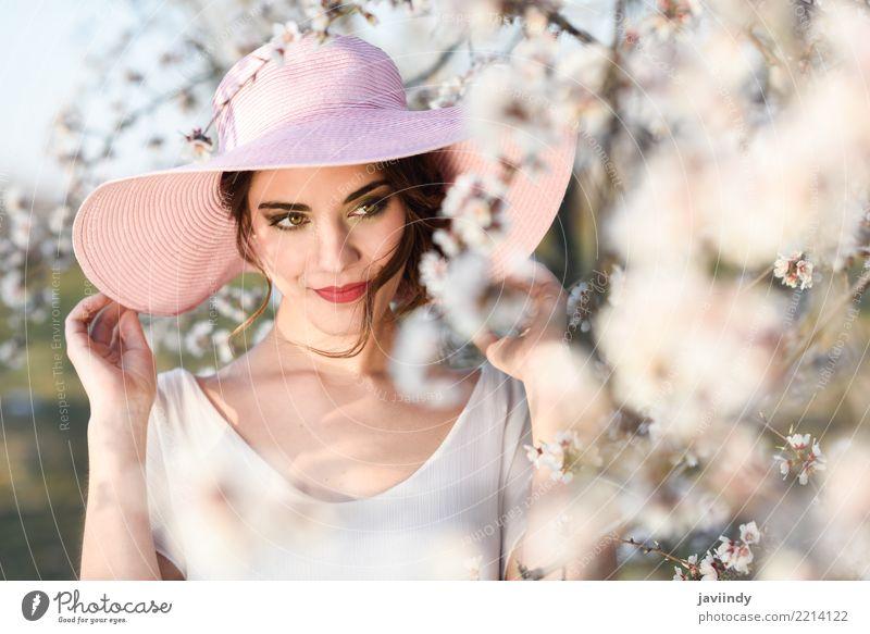 Frau in der geblühten Zeit des Feldes im Frühjahr Stil Glück schön Gesicht Mensch Erwachsene Natur Baum Blume Blüte Park Mode Kleid Hut brünett rosa weiß