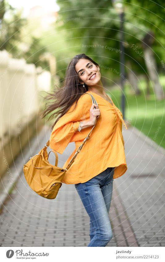 Junge Frau mit dem beweglichen Haar, das zufällige Kleidung trägt Lifestyle Stil Glück schön Haare & Frisuren Mensch Erwachsene Wind Straße Mode Bekleidung