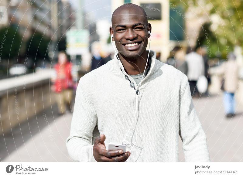 Schwarzer junger Mann mit einem Smartphone in seiner Hand Mensch Jugendliche schön 18-30 Jahre schwarz Gesicht Erwachsene Straße Lifestyle Glück Mode modern