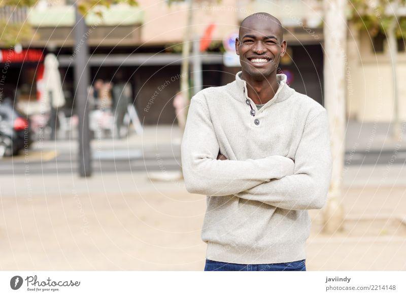 Schwarzer junger Mann mit den Armen kreuzte das Lächeln im städtischen Hintergrund Mensch Jugendliche schön 18-30 Jahre schwarz Gesicht Erwachsene Straße