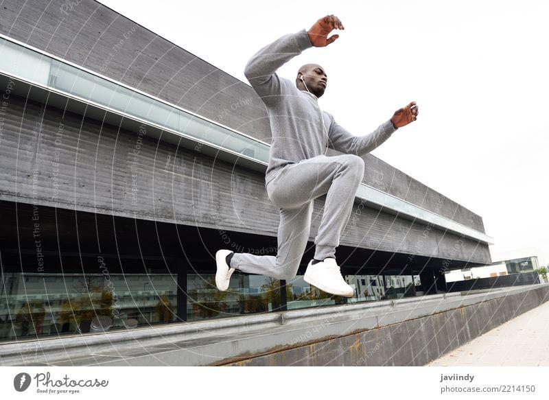 Ein schwarzer Mann, der im urbanen Hintergrund springt. Lifestyle Sport Joggen Mensch Erwachsene Straße Fitness springen rennen Afrikanisch Bewegung weitergeben
