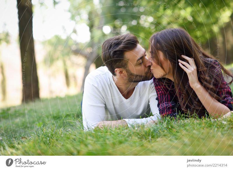 Schöne junge Paare, die auf Gras in einem städtischen Park küssen Frau Natur Jugendliche Mann Sommer schön grün Freude 18-30 Jahre Erwachsene Lifestyle Herbst