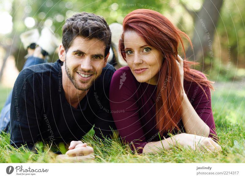 Schöne junge Paare, die auf Gras in einem städtischen Park legen. Frau Mensch Natur Jugendliche Mann Sommer schön grün Freude 18-30 Jahre Erwachsene Lifestyle