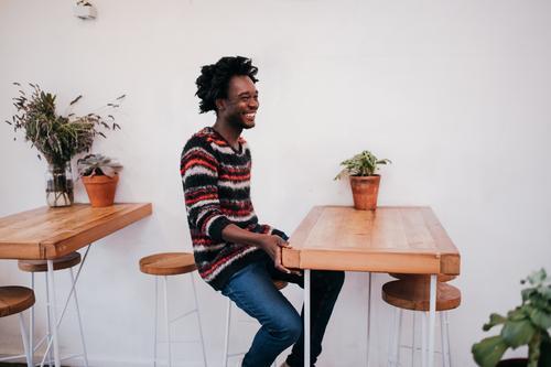 Junger glücklicher afroamerikanischer Mann, der im Café sitzt. Lifestyle Freude Erholung Tisch Restaurant Mensch Erwachsene Jugendliche Afro-Look Holz Lächeln