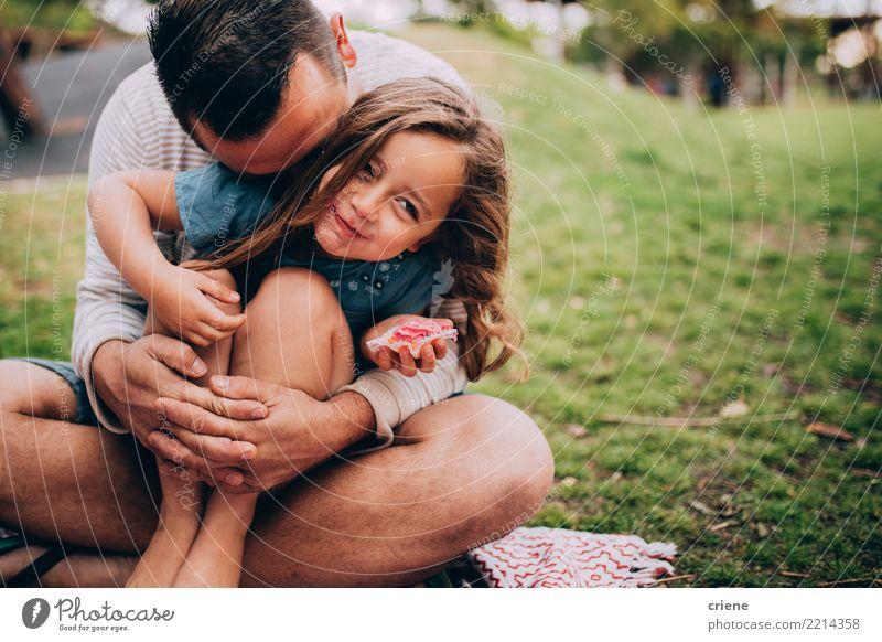 Vater und Tochter bei einem Picknick im Park Kind Mensch Freude Mädchen Essen Erwachsene Lifestyle Wiese Gefühle Gras Familie & Verwandtschaft klein Glück