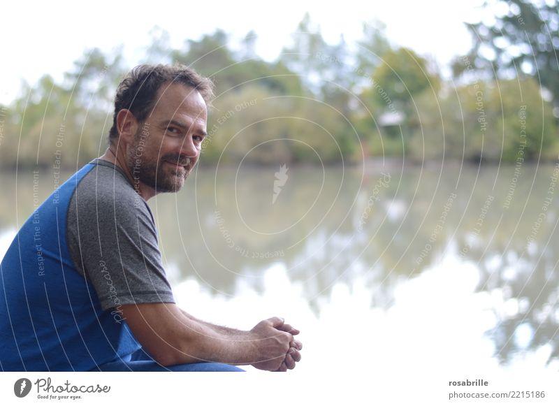 dunkelhaariger Mann mit Bart im mittleren Alter hockt in einer Lichtung am Weiher und schaut über die Schulter in die Kamera Freizeit & Hobby Mensch Erwachsene