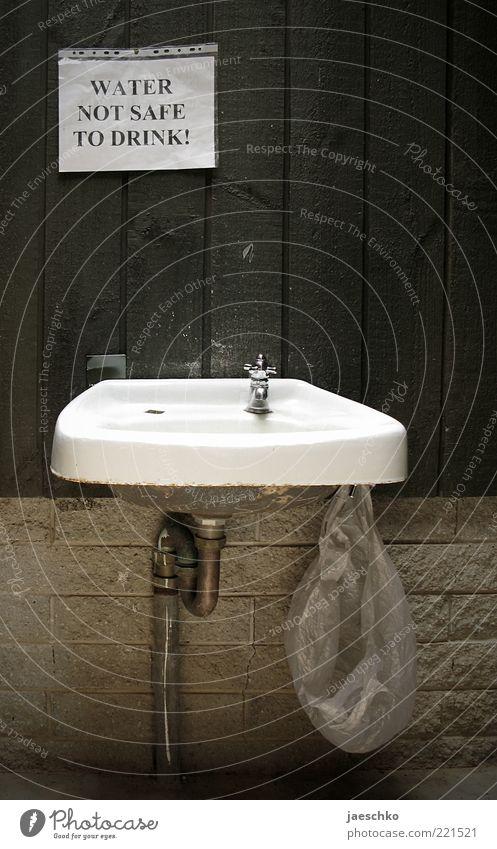 Durstig? Wand Holz Stein Mauer dreckig Trinkwasser einfach Sauberkeit Hinweisschild Verfall bizarr schäbig wenige Durst Müllbehälter Wasserhahn