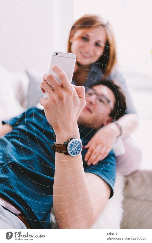 Paare, die online zu Hause auf Smartphone durchstöbern Lifestyle Erholung Freizeit & Hobby Sofa sprechen Telefon Technik & Technologie Frau Erwachsene Mann