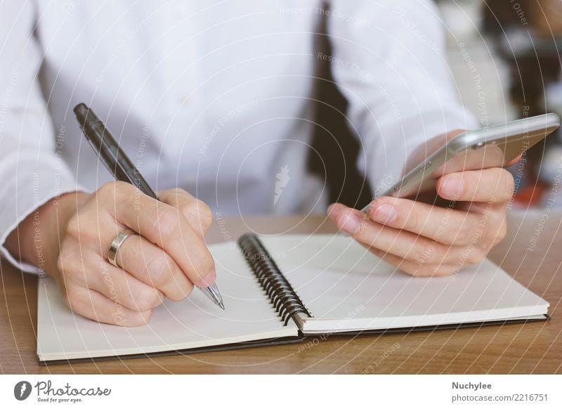 Frauenhände unter Verwendung des Smartphone und Schreiben des Notizbuches Mann weiß Hand Erwachsene Business Arbeit & Erwerbstätigkeit Büro modern Papier
