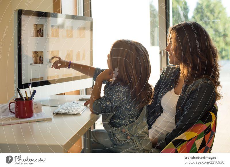 Mutter und Tochter, die ihre Fotos auf Computer aufpassen Glück Freizeit & Hobby Schreibtisch Kind Technik & Technologie Internet Frau Erwachsene Eltern