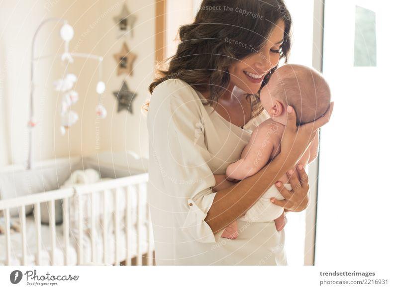 Junge Mutter, die ihr Baby im Schlafzimmer hält Kind Frau schön weiß Erwachsene Liebe Familie & Verwandtschaft klein Glück Kindheit schlafen heimwärts Eltern
