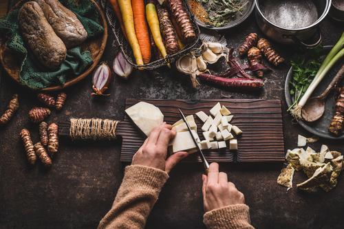Hände schneiden Gemüse auf rustikalem Küchentisch Lebensmittel Ernährung Bioprodukte Vegetarische Ernährung Diät Topf Messer Stil Gesunde Ernährung