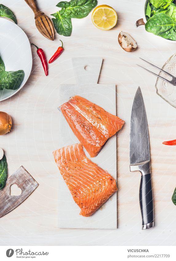 Lachsfilet auf wießem Schneidebrett mit Messer Lebensmittel Fisch Gemüse Salat Salatbeilage Kräuter & Gewürze Ernährung Mittagessen Abendessen Bioprodukte Diät