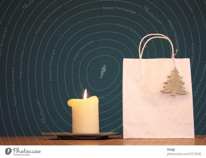 Papiertasche mit Holztannenbaum als Dekoration und brennende Kerze stehen auf einem Tisch vor dunkelblauem Hintergrund Design Dekoration & Verzierung Verpackung