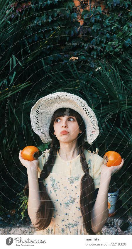 Junge Retro- Frau, die Persimonen hält Mensch Natur Jugendliche Junge Frau schön grün weiß 18-30 Jahre Erwachsene Umwelt Gesundheit lustig feminin Lebensmittel