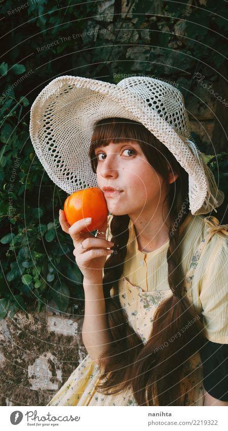 Junge und altmodische Frau, die eine Persimone hält Lebensmittel Gemüse Frucht Orange Ernährung Essen Lifestyle Stil schön Gesundheit Gesunde Ernährung Wellness