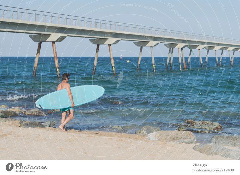 Junger attraktiver Surfer, der sein Surfbrett am Strand hält Lifestyle Freude Ferien & Urlaub & Reisen Sommer Sonne Meer Wellen Sport Mann Erwachsene