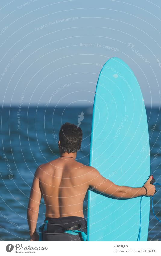 Surfer, der sein Surfbrett am Strand hält Lifestyle Freude Ferien & Urlaub & Reisen Sommer Meer Wellen Sport Mann Erwachsene Jugendliche Himmel Wolken Küste