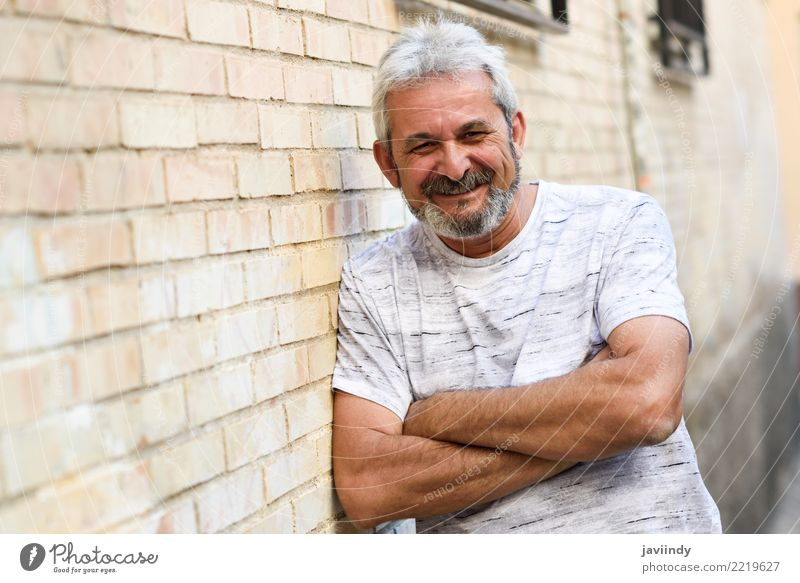 Reifer Mann, der an der Kamera im städtischen Hintergrund lächelt. Mensch alt weiß Erwachsene Straße Lifestyle Glück 45-60 Jahre Lächeln Fröhlichkeit Bekleidung