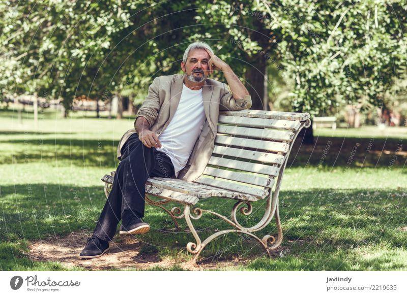 Nachdenklicher reifer Mann, der auf einer Bank in einem städtischen Park sitzt. Mensch alt Erwachsene Straße Lifestyle Glück 45-60 Jahre Bekleidung