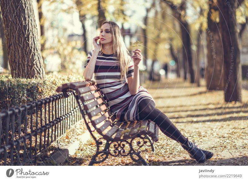 Junge blonde Frau, die auf einer Bank in der Straße sitzt Lifestyle elegant Stil schön Haare & Frisuren Mensch feminin Junge Frau Jugendliche Erwachsene 1