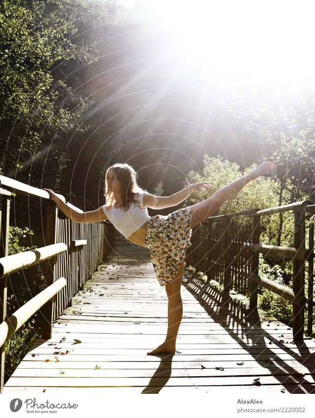 junge, sportlichen Frau steht barfuß und im Gegenlicht auf einer Holzbrücke im Wald und hält in Tänzerpose ein Bein gestreckt und gerade nach oben Freude schön