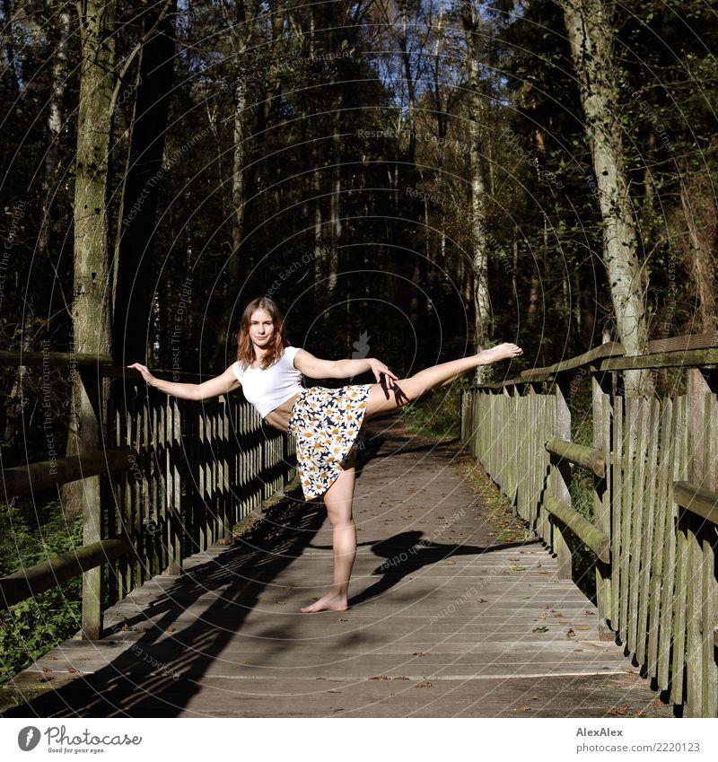 Junge, sehr sportliche Frau steht barfuß auf einer Holzbrücke im Wald und macht barfuß und bauchfrei eine Tanzpose Freude schön Fitness Leben Turnen Junge Frau