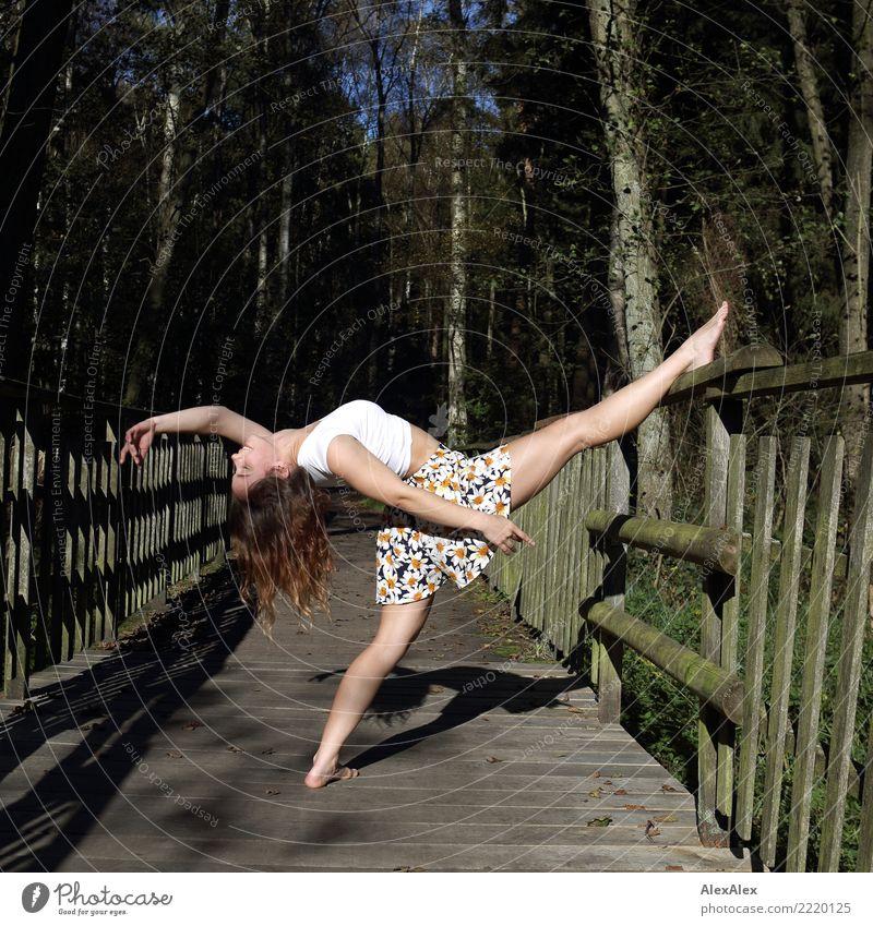 Junge, sehr sportliche und schlanke Frau macht eine Tanz- Streckfigur auf dem Gelände eine Holzbrücke im Wald, sie ist barfuß und lehnt ein Bein auf das Geländer, den Kopf ganz nach hinten
