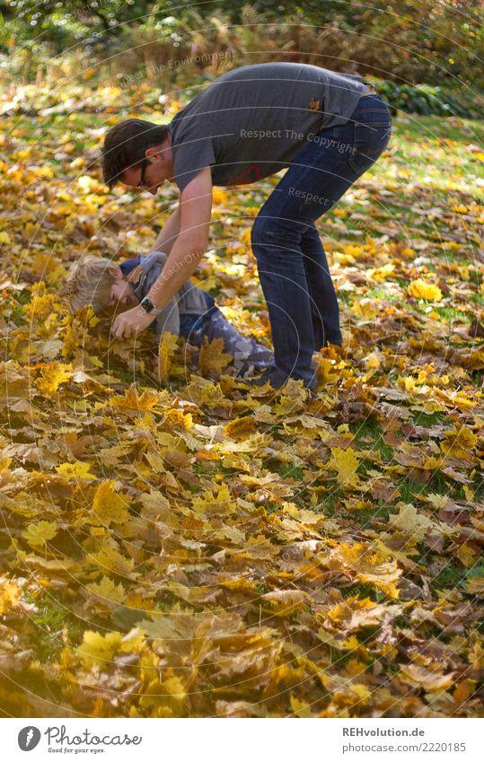 Mann spielt mit Kind im Herbstlaub Schwache Tiefenschärfe Unschärfe Sonnenlicht Tag Textfreiraum links Außenaufnahme Farbfoto Bewegung Lebensfreude