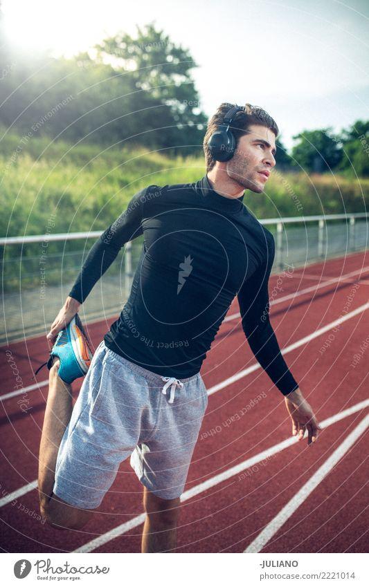 Junger Mann beim Stretching auf der Laufstrecke mit Kopfhörern Trinkwasser Lifestyle Freude Körper Gesundheit Gesunde Ernährung Gesundheitswesen sportlich