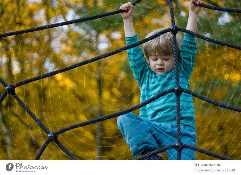 Kind klettert auf dem Spielplatz im Herbst Schwache Tiefenschärfe Unschärfe Tag Außenaufnahme Gedeckte Farben Farbfoto Kletterseil Seil Netz Klettern Erfahrung