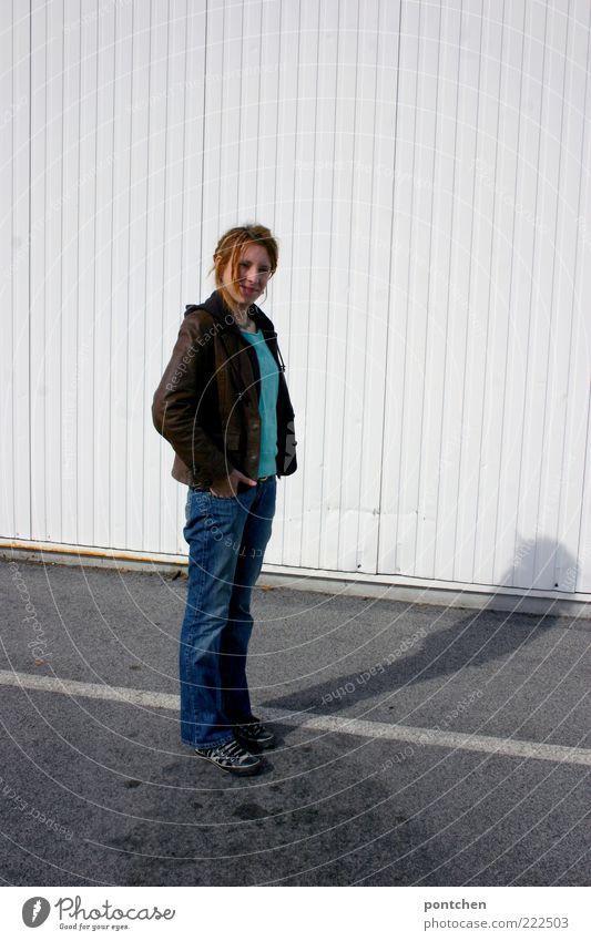 rumstehen Mensch Jugendliche Hand weiß Erwachsene Haare & Frisuren hell blond Fassade stehen einzigartig Jeanshose Junge Frau dünn Turnschuh Parkplatz