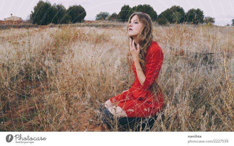 Die junge blonde Frau, die ein rotes Kleid trägt, wartet auf einem Gebiet Mensch Natur Ferien & Urlaub & Reisen Jugendliche Junge Frau Sommer schön Landschaft